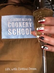 Jamie Oliver Cookery School Apron with glass of prosecco
