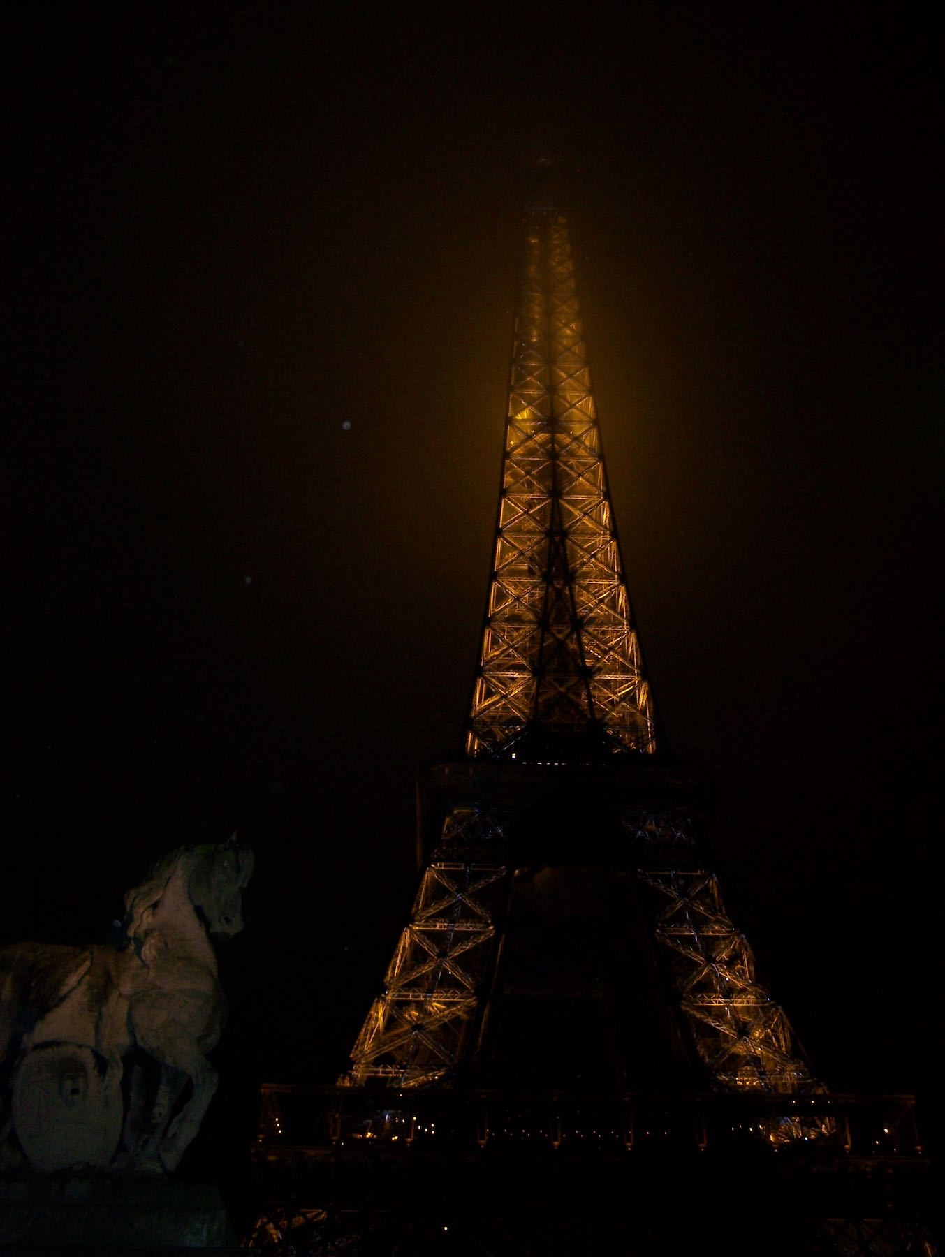 Eiffel tower in Paris at night surrounded by clouds