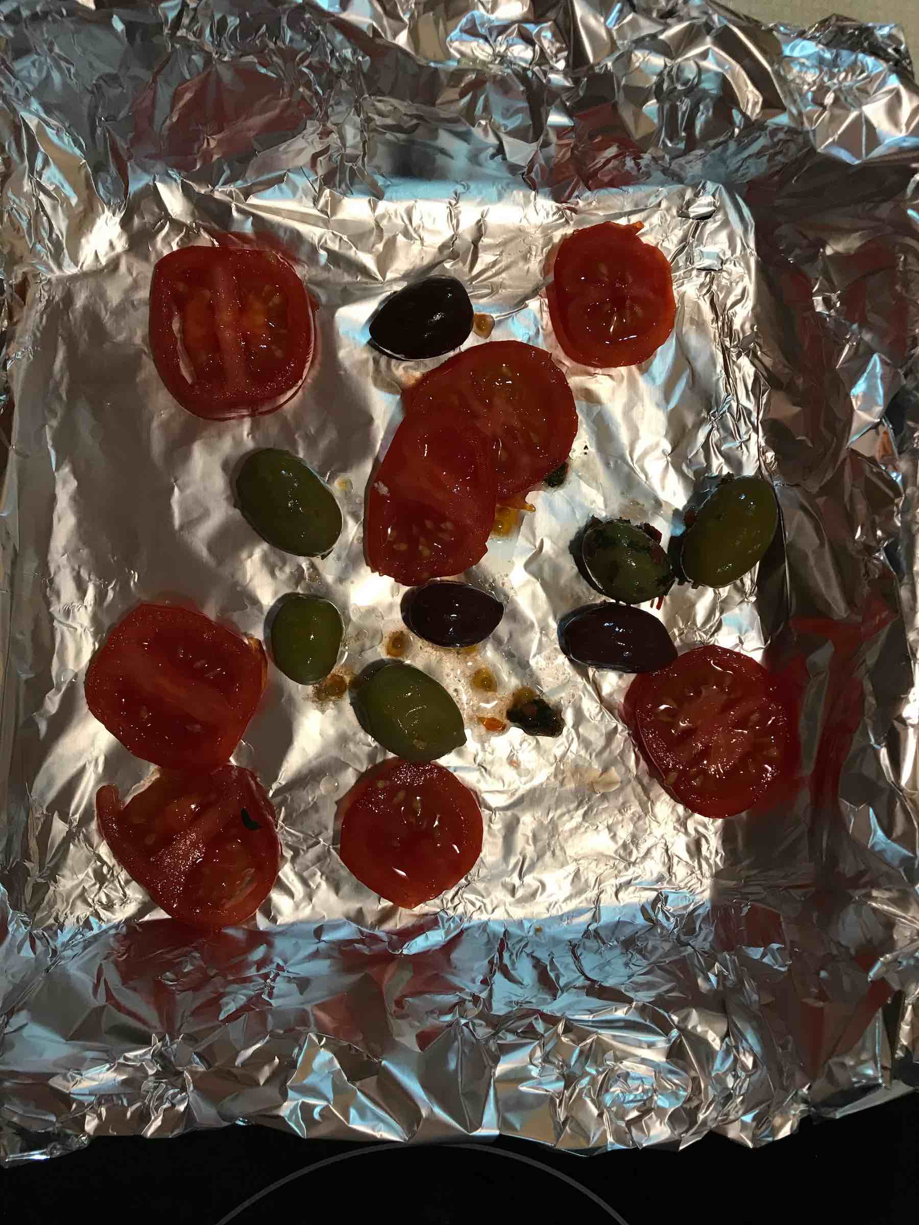 Tomatoes and olives on foil